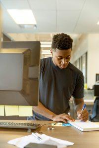 Teenage boy writing in library