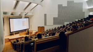 Students listening to college lecture in large auditorium